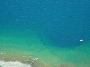 The Middle Island sinkhole is open to Lake Huron creating a gradient of biological activity. A 9-meter Whaler is also visible in this aerial photo for a sense of scale. Image courtesy of Scott Kendall and Bopi Biddanda, Grand Valley State University.