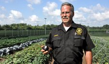 Corrections Officer Mike Dangelo with a pepper grown by inmates in Ohio's Lorain County jail.
