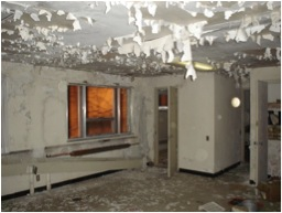 Asbestos is present in building walls, flooring, and insulation. A building is shown with paint crumpling from the walls. Photo by: E. Pernicone