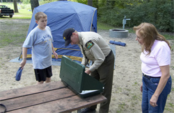 A DNR officer demonstrates the finer points of camping. Photo: Michigan DNR