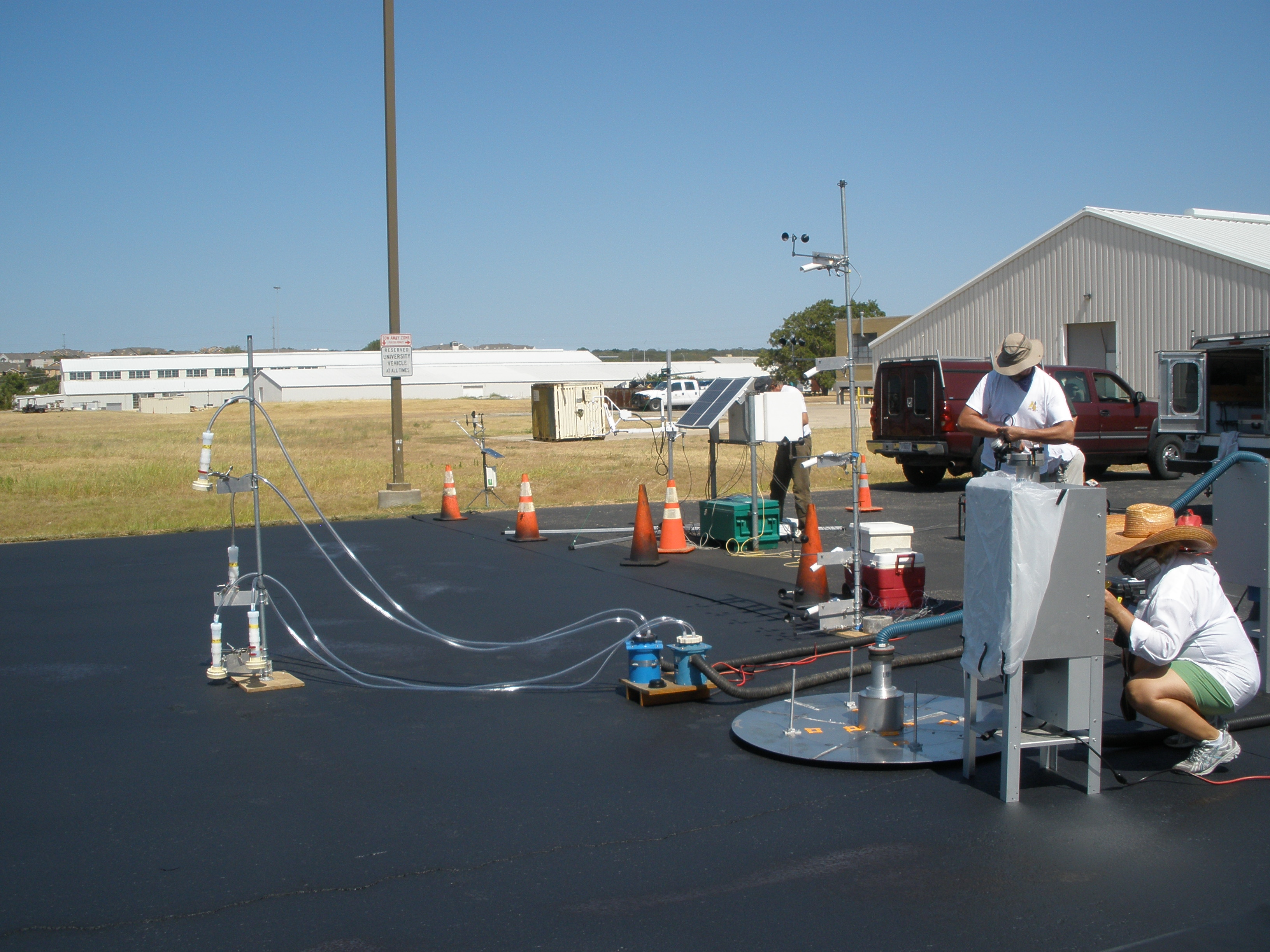 Researchers studying air quality and toxicity of runoff in a parking lot sealed with coal-tar. Credit: Barbara Mahler, USGS Research Hydrologist