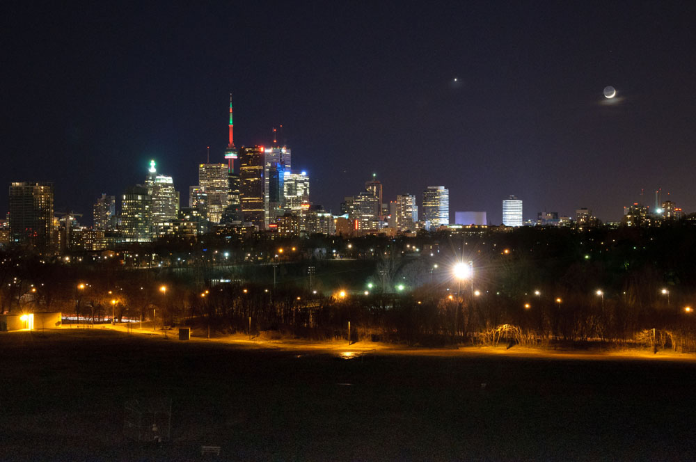 The day after Christmas 2011, the two-day-old crescent moon and Venus appeared in the sky over Toronto, Ontario. The darker portion of the moon, ordinarily invisible during its crescent stage, is lit by earthshine, sunlight reflected by the daytime side of the earth upon the moon. Photo by Andrew Yee.