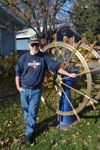 Capt. Tom Mackay, a retired captain from the Vista Fleet, stands with a big lake freighter wheel in the front yard of his home on Park Point. Photo by Jenae Peterson.