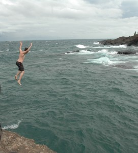 A young man dives off of the Blackrocks cliff edges. Photo: Becky McKendry.