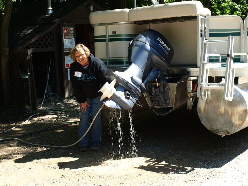 Sallyanne Morris flushes a boat engine, removing possible hitchhiking invasive species, before the boat enters the lake. Photo: Leslie Mertz.