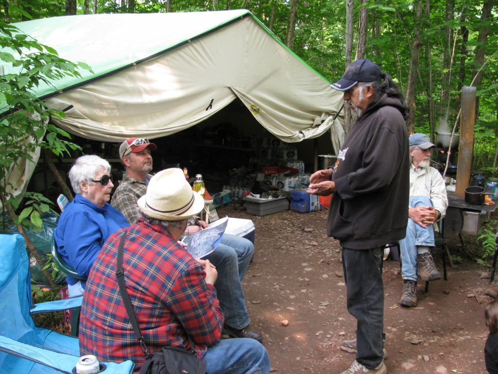 Visitors to the harvest camp listen to Mel Gasper, camp manager from the Lac Courte Oreilles band, as he talks about the Penokee Range and the proposed iron mine. Photo: Ron Seely/Wisconsin Center for Investigative Journalism.