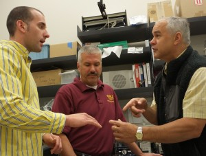 Lee Schoen, left, explains to Donald Uzarski, center, and Jim Student how he makes thin slices of fish ear bones. Photo: Leslie Mertz.