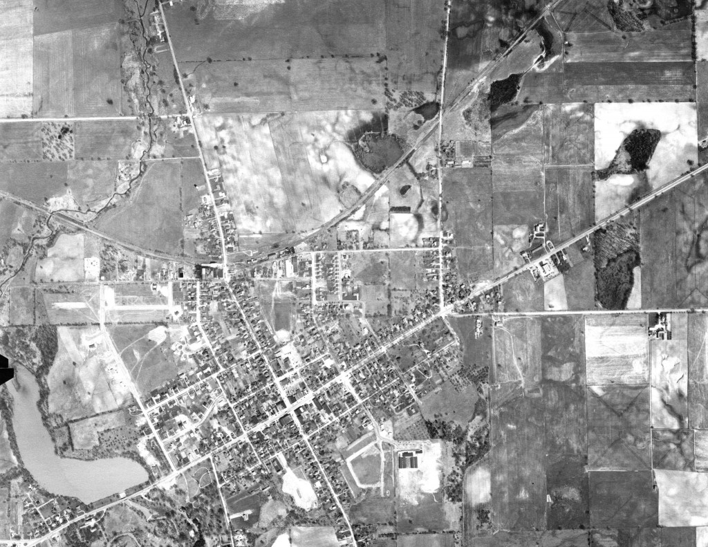 Saline, 1956: Sixteen years later, the city shows small signs of growth. The land next to the southeast corner of Mill Pond has been filled in by new housing, and down Michigan Ave. to the east of the city's center a small shopping center has developed.