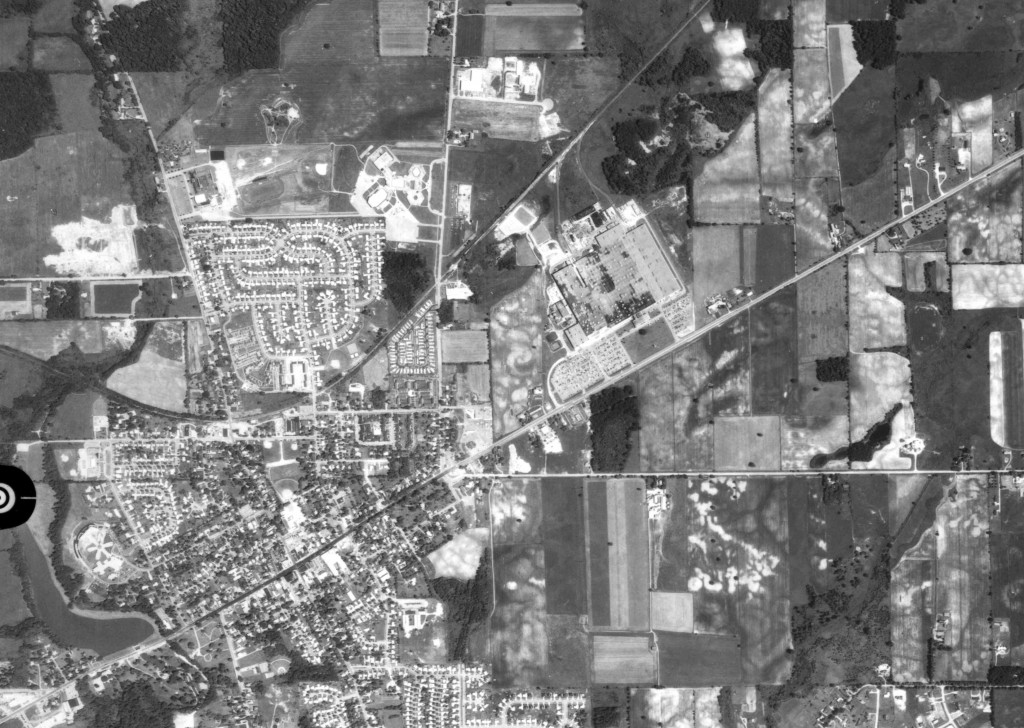 Saline, 1978: In this zoomed out photo, construction has finished on both schools on the north end of the town. Saline Middle School is to the west and the high school is to the east. The shopping center on Saline's east end has grown significantly, but it is still surrounded largely by farmland.