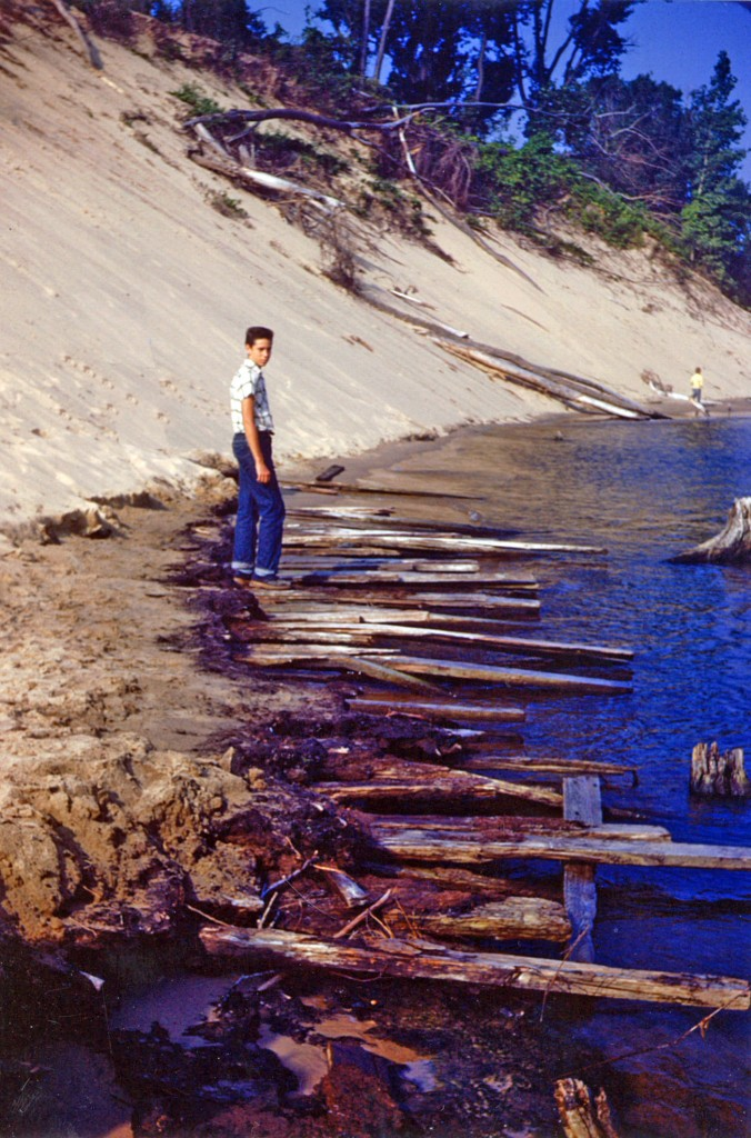 Jack Sheridan stands on Singapore era slabs protruding from the sand. ca. 1953 (Image: Jack Sheridan)