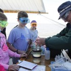 Volunteer educator and retired Dow chemist Dick Crooks shows students aboard the Appledore how to find dissolved oxygen using the Winkler reaction. Image: Appledore