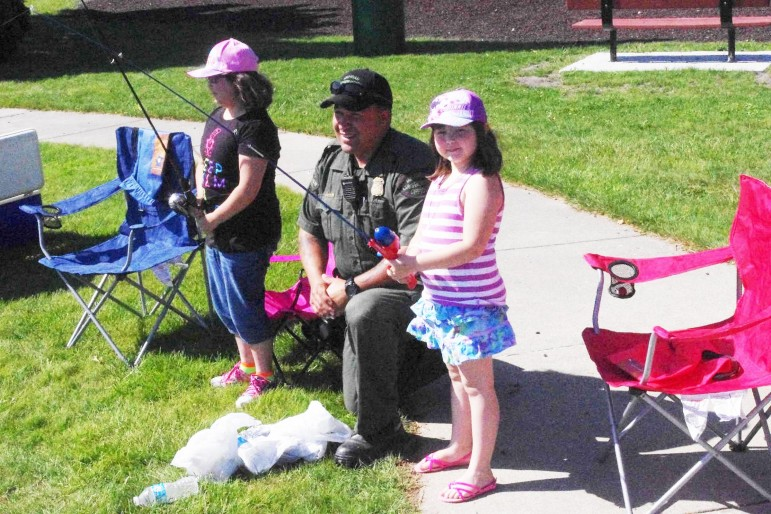 Department of Natural Resources officer Quincy Gowenlock gives advice to Maria and Elizabeth Romero of St. Louis competing in the Pine River Fishing Derby. Image: John Evans, Gratiot County Herald