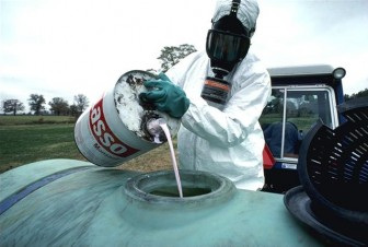 Hazardous herbicide being poured to be sprayed on food crops. Image: United States Department of Agriculture