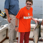 Young boy and father catching a Chinook salmon on Lake Michigan. Image: Eamon Devlin