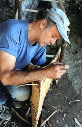 Tom Byers uses spruce root to lash together two sides of a birch bark canoe. Image:  Courtesy Tom Byers