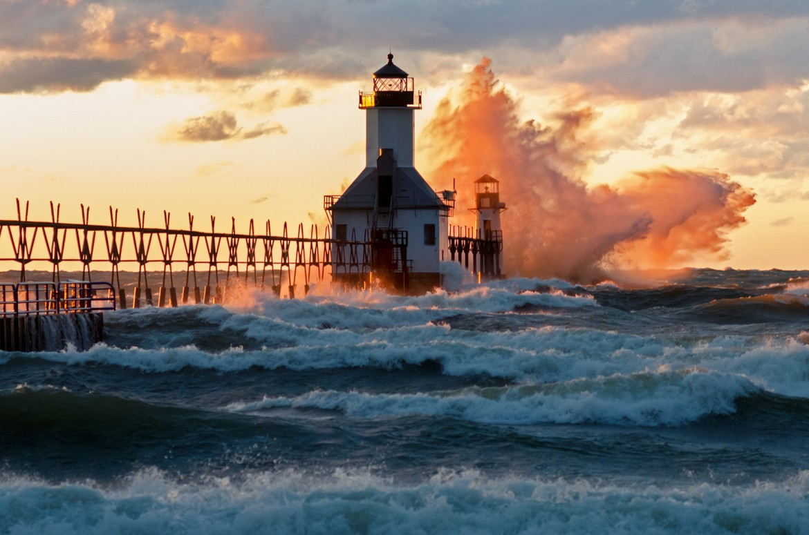 Twenty foot waves pound a Lake Michigan lighthouse, spraying water in a colorful burst.