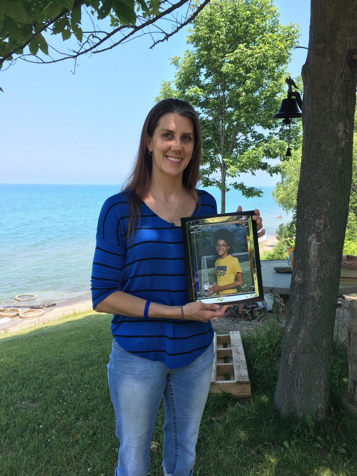 Melissa Zirkle holds photo of son Jermaine. Image: Elizabeth Miller.