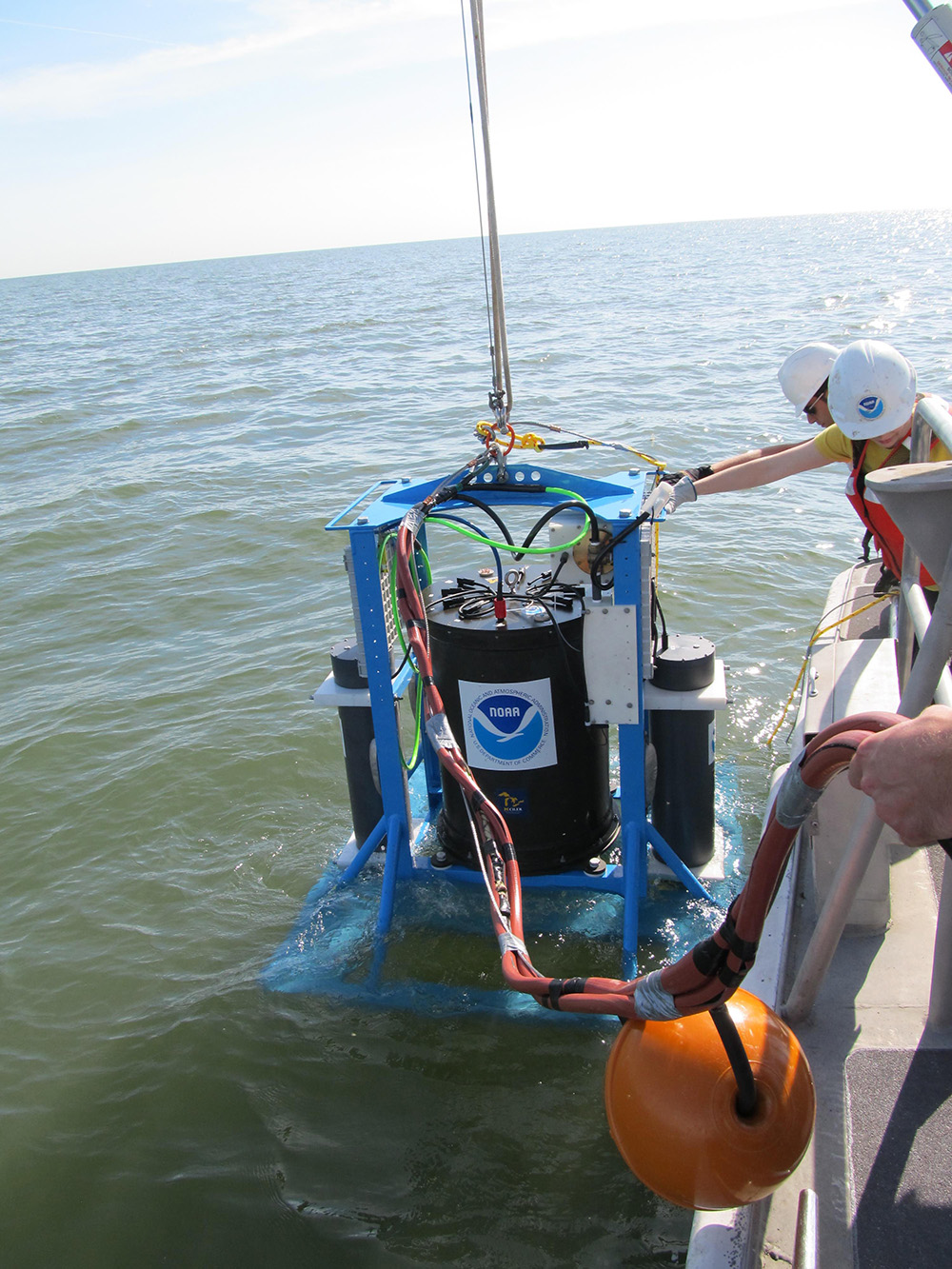 The sealed Environmental Sample Processor is lowered into a lake. Image: NOAA.